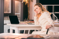 Thoughtful businesswoman in suit sitting at table in office Stock Photos