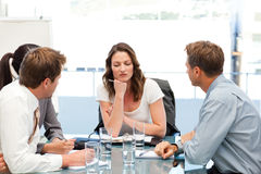 Thoughtful businesswoman at a table with her team Stock Image