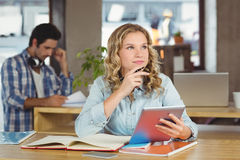 Thoughtful businesswoman with tablet in office Royalty Free Stock Images