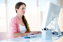Thoughtful businesswoman typing on her computer Stock Photography