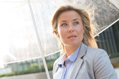 Thoughtful businesswoman with umbrella outdoors Royalty Free Stock Photos