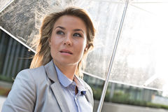 Thoughtful businesswoman with umbrella outdoors Stock Images
