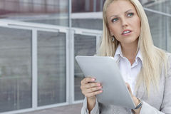 Thoughtful businesswoman using digital tablet while looking away against office building Stock Photo
