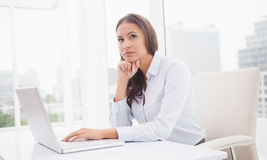 Thoughtful businesswoman using laptop at her desk Stock Photo