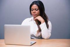 Thoughtful businesswoman using laptop Stock Photos