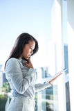 Thoughtful businesswoman using tablet Stock Images
