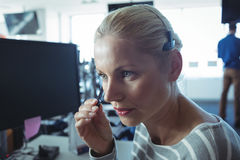 Thoughtful businesswoman wearing headphones Stock Photo