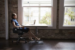 Thoughtful Businesswoman Working On Laptop By Window Stock Photo