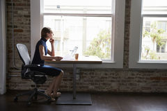 Thoughtful Businesswoman Working On Laptop By Window Royalty Free Stock Photos