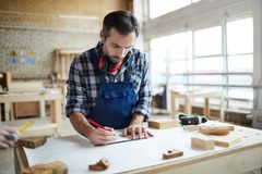 Thoughtful carpenter making sketch stock image