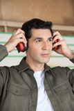 Thoughtful Carpenter Wearing Ear Protectors Stock Photo