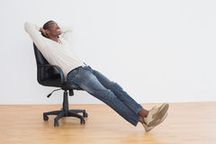 Thoughtful casual Afro man sitting on office chair in empty room Stock Photos