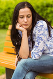 Thoughtful casual brunette sitting on bench Stock Photo
