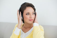 Thoughtful casual brunette in yellow cardigan listening to music with headphones Stock Images
