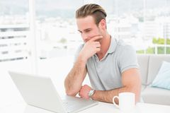 Thoughtful casual businessman working with laptop Stock Photo