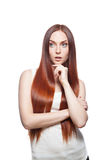 Thoughtful casual red-haired female on white. Vertical studio portrait of young attractive green-eyed caucasian female with long natural straight shiny red hair Royalty Free Stock Photo