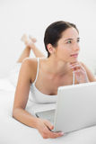 Thoughtful casual woman with laptop in bed. Thoughtful casual young woman with laptop in bed at home Stock Image