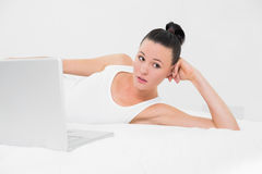 Thoughtful casual woman with laptop in bed. Thoughtful casual young woman with laptop lying in bed Stock Photos