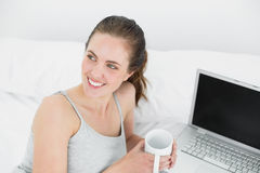 Thoughtful casual woman with laptop and coffee cup in bed Stock Images