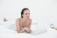 Thoughtful casual woman using laptop in bed Stock Photography