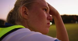 Female soccer player sitting on the ground on soccer field. 4k. Thoughtful Caucasian female soccer player sitting on the ground evaluating the training on soccer stock video footage