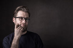 Thoughtful caucasian man in casual t-shirt and glasses Royalty Free Stock Photos
