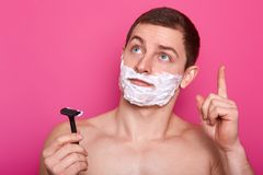Thoughtful Caucasian man with shaving gel, raises fore finger, idea in mind, holds sharp razor in one hand, keeps gaze upwards, stock image
