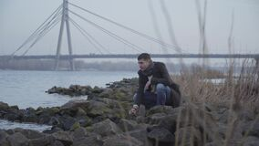 Thoughtful Caucasian young man sitting on riverbank and throwing rocks in water. Portrait of sad handsome guy in