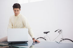 Thoughtful causal businessman using laptop Royalty Free Stock Images