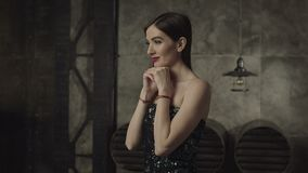 Thoughtful charming woman with hands on chin. Portrait of thoughtful charming brunette woman in evening dress and makeup, propped chin on hands, looking with stock video footage