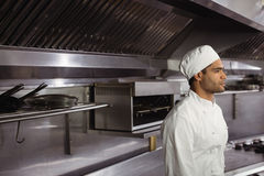 Thoughtful chef standing in commercial kitchen. At restaurant stock images