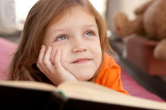 Thoughtful child. Thoughtful little girl with a book Royalty Free Stock Image