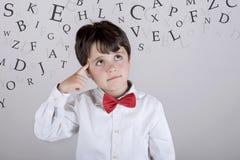 Thoughtful child. Alphabet. Composite image of thoughtful boy Stock Photography