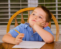 Thoughtful child doing his homework. At kitchen table at home royalty free stock image