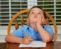 Thoughtful child doing his homework. At kitchen table at home stock photo
