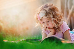 Thoughtful child girl learning and reading book on summer vacation in the garden Royalty Free Stock Photography