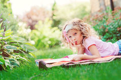 Thoughtful child girl reading book in summer sunny garden Stock Photo