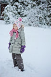 Thoughtful child girl on the walk in winter garden with falling snow Royalty Free Stock Photography