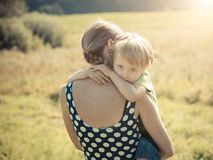 Thoughtful child hugging mother stock photo