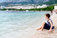 Thoughtful child sitting on the beach. And throwing little stones Royalty Free Stock Photo