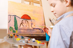Thoughtful child using pallet in the art studio. Process of creating something unique. Attentive involved skilled child sitting in the art studio and having Royalty Free Stock Image