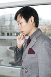 A Thoughtful Chinese Business man. Pondering about whether to agree or not on a business proposal Stock Photo