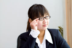 Thoughtful chinese businesswoman. Thoughtful young chinese business woman in office Royalty Free Stock Image