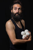 Thoughtful circus juggler miming with his juggling balls Royalty Free Stock Photography