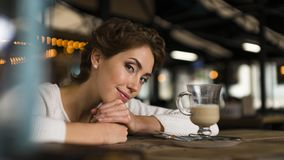 Thoughtful concept. Woman dreaming at a cafe while gazing through the window glass. Thoughtful concept. Woman dreaming at a cafe while gazing through the window Stock Images