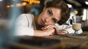 Thoughtful concept. Woman dreaming at a cafe while gazing through the window glass. Thoughtful concept. Woman dreaming at a cafe while gazing through the window Royalty Free Stock Photography