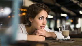 Thoughtful concept. Woman dreaming at a cafe while gazing through the window glass. Thoughtful concept. Woman dreaming at a cafe while gazing through the window Royalty Free Stock Images