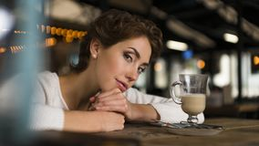 Thoughtful concept. Woman dreaming at a cafe while gazing through the window glass. Thoughtful concept. Woman dreaming at a cafe while gazing through the window Stock Photography