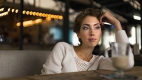 Thoughtful concept. Woman dreaming at a cafe while gazing through the window glass. Thoughtful concept. Woman dreaming at a cafe while gazing through the window Royalty Free Stock Photos