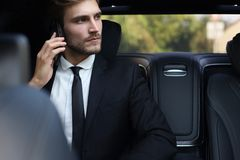 Thoughtful confident businessman talking on the phone while sitting in the car royalty free stock photography
